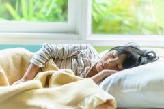 Asiatisches Mädchen, das auf dem Bett bedeckt mit Decke schläft Lizenzfreies Stockfoto