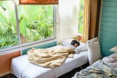 Asiatisches Mädchen, das auf dem Bett bedeckt mit Decke schläft Lizenzfreie Stockfotografie