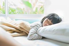 Asiatisches Mädchen, das auf dem Bett bedeckt mit Decke schläft Lizenzfreie Stockfotos