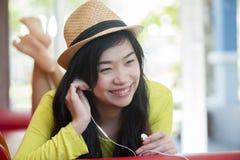Asiatisches Mädchen, das auf dem Sofa liegt und Musik hört stockfotos