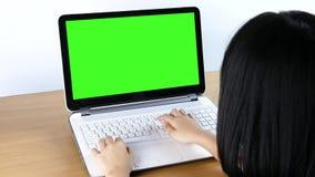 Asiatisches Mädchen, das auf einer Laptop-Computer schreibt stock footage