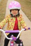 Asiatisches Mädchen, das auf Fahrrad mit Sturzhelm rideing ist Stockfoto