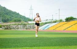 Asiatisches Mädchen, das auf Fußballplatz rüttelt stockfotos