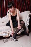 Asiatisches Mädchen, das auf Schuhe sich setzt Stockfoto