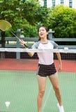 Asiatisches Mädchen, das Badminton auf dem Gericht spielt stockbilder