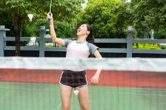 Asiatisches Mädchen, das Badminton auf dem Gericht spielt lizenzfreie stockbilder