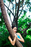 Asiatisches Mädchen, das Baum umarmt Lizenzfreie Stockbilder