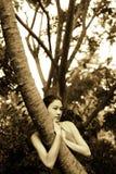 Asiatisches Mädchen, das Baum umarmt Stockbild