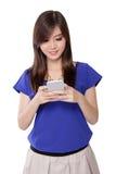 Asiatisches Mädchen, das beim Simsen, lokalisiert auf Weiß lächelt Lizenzfreie Stockfotos