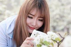 Asiatisches Mädchen, das Bilder von den Blumen macht Stockbild