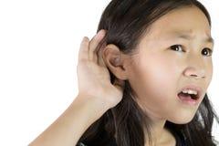 Asiatisches Mädchen, das durch hand's bis zum Ohr hört stockfoto
