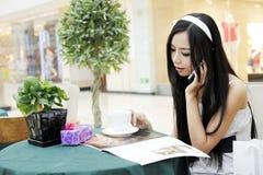 Asiatisches Mädchen, das durch Telefon benennt. Lizenzfreie Stockfotografie
