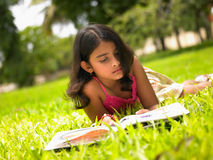 Asiatisches Mädchen, das ein Buch im Park liest Stockfoto