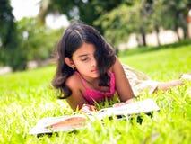 Asiatisches Mädchen, das ein Buch im Park liest Stockfotos