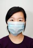 Asiatisches Mädchen, das eine Schablone trägt Stockfotografie