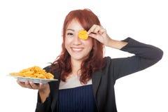 Asiatisches Mädchen, das einen Kartoffelchip vor ihrem Auge hält Stockbilder