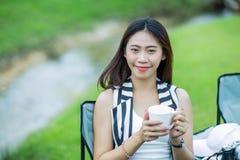 Asiatisches Mädchen, das einen Tasse Kaffee nahe dem Strom hält Stockbilder
