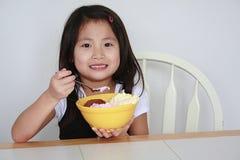 Asiatisches Mädchen, das Eiscremeschüssel isst Lizenzfreie Stockbilder