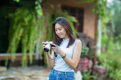 Asiatisches Mädchen, das Foto auf Kamera überprüft Lizenzfreie Stockbilder