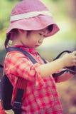 Asiatisches Mädchen, das Fotos in der Digitalkamera überprüft Weinlesebildst. Stockbilder
