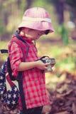 Asiatisches Mädchen, das Fotos in der Digitalkamera überprüft Weinlesebildst. Stockfoto