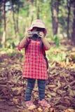 Asiatisches Mädchen, das Fotos durch Digitalkamera im Garten macht Weinlese-PU Lizenzfreies Stockfoto