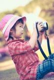 Asiatisches Mädchen, das Fotos unter Verwendung der Weinlesefilmkamera im Garten macht VI Stockfotos