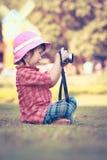 Asiatisches Mädchen, das Fotos unter Verwendung der Weinlesefilmkamera im Garten macht VI Stockbild