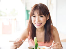 Asiatisches Mädchen, das Gemüsenudeln isst Lizenzfreie Stockfotografie