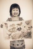 Asiatisches Mädchen, das ihr Grafik, Atelieraufnahme, Weinlesebildschweinestall zeigt Stockfotografie