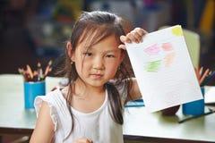 Asiatisches Mädchen, das ihre Zeichnung zeigt Stockfotos