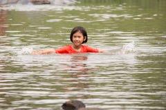 Asiatisches Mädchen, das ist, genießen Schwimmen Stockbild