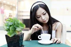 Asiatisches Mädchen, das Kaffee trinkt Lizenzfreie Stockfotografie