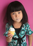 Asiatisches Mädchen, das kleinen Kuchen isst Stockbild