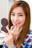 Asiatisches Mädchen, das Lippenstift anwendet lizenzfreies stockfoto