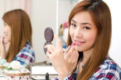 Asiatisches Mädchen, das Lippenstift anwendet stockfoto