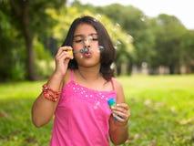 Asiatisches Mädchen, das Luftblasen bildet Stockbilder