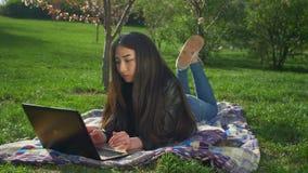 Asiatisches Mädchen, das mit ihrem Notizbuch liegt auf Rasen arbeitet stock video