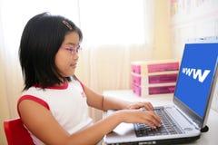 Asiatisches Mädchen, das mit Laptop-Computer auf Tabelle spielt Lizenzfreies Stockfoto
