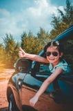 Asiatisches Mädchen, das mit perfektem Lächeln beim Sitzen im Auto lächelt Lizenzfreies Stockfoto