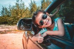 Asiatisches Mädchen, das mit perfektem Lächeln beim Sitzen im Auto lächelt Stockbild