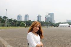 Asiatisches Mädchen, das in Monas, Jakarta mit Ansicht von Wolkenkratzern aufwirft stockbilder