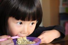 Asiatisches Mädchen, das Nudeln isst Stockfotos