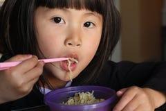 Asiatisches Mädchen, das Nudeln isst Stockbilder