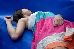 Asiatisches Mädchen, das sich auf einem blauen Hintergrund hinlegt Stockbilder