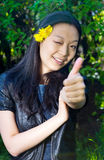 Asiatisches Mädchen, das sich Daumen zeigt Stockfoto
