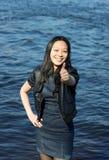 Asiatisches Mädchen, das sich Daumen zeigt Stockfotografie