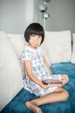 Asiatisches Mädchen, das sich zu Hause entspannt Stockbilder