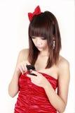 Asiatisches Mädchen, das sms sendet. Stockfotografie