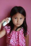 Asiatisches Mädchen, das Temperatur nimmt Stockfoto